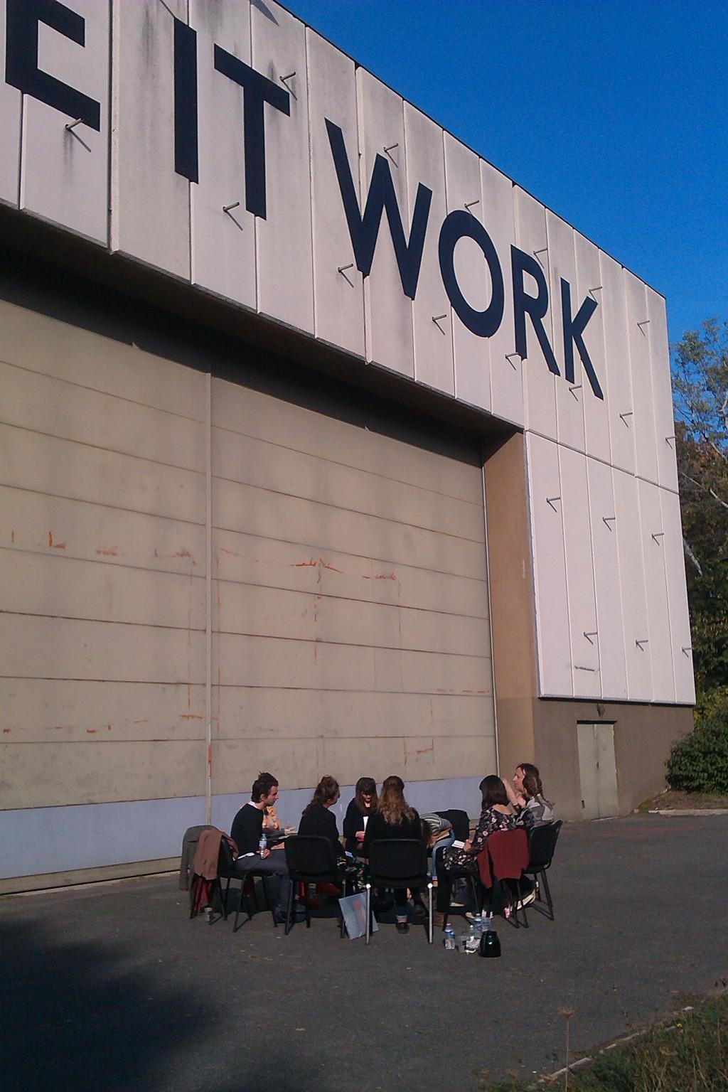 Les étudiants sont assis en cercle dehors devant la scène d'été des Amandiers. Make it work!