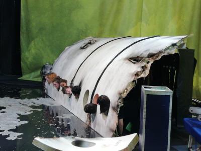 Les 8 étudiants passent leurs têtes par les hublots du décor d'avion de Crash Park